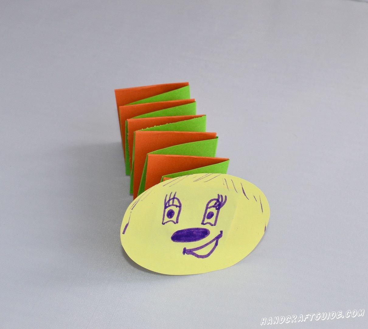 Из бумаги желтого цвета мы вырезаем овал, на котором рисуем личико нашей гусеницы