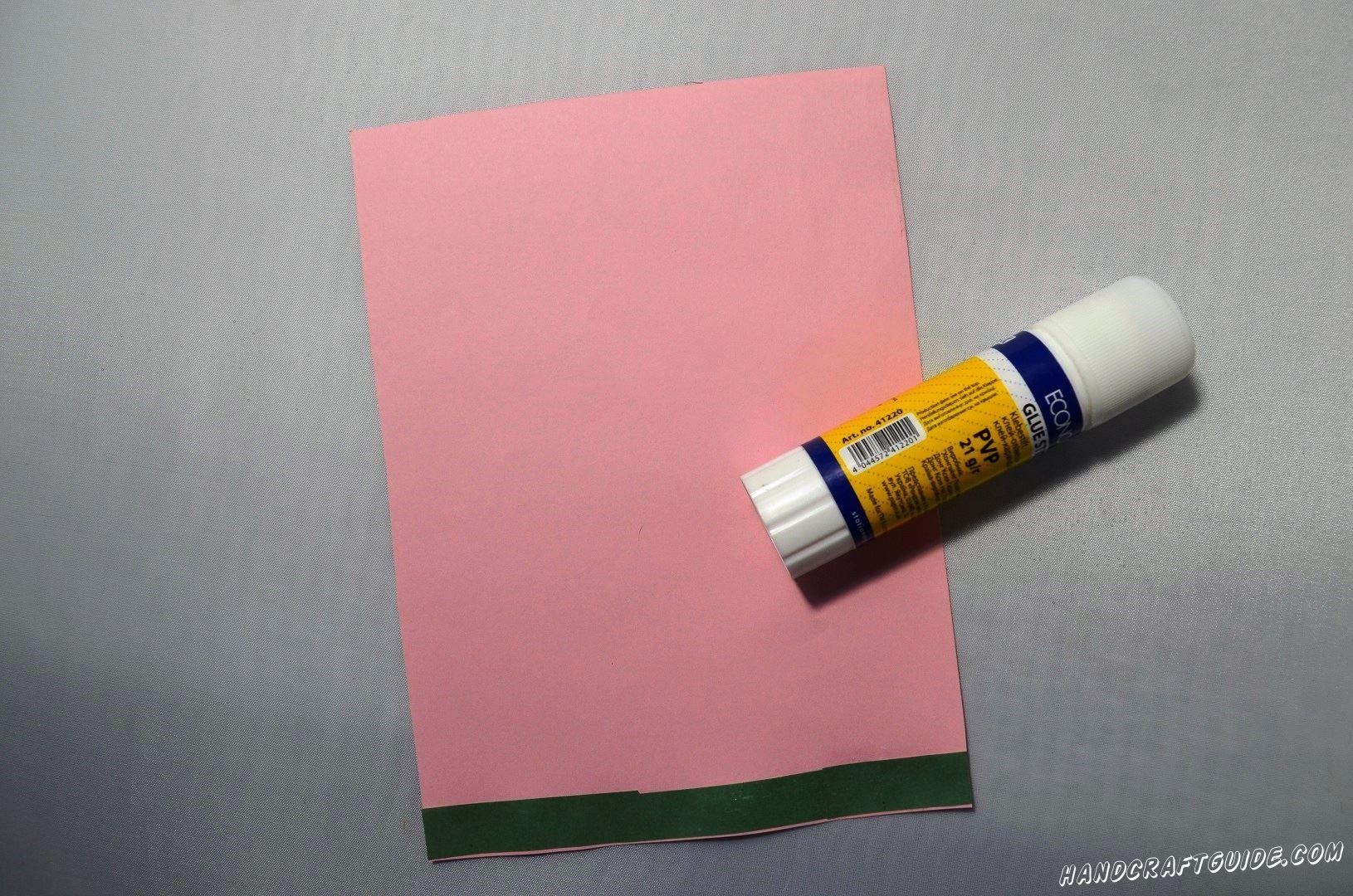 Осталось сделать соответствующий фон для нашего цветка. Берем лист розовой бумаги, на него накаливаем меньший прямоугольник светлого оттенка и ещё меньший голубой прямоугольник. Снизу мы наклеиваем зелёную полоску.