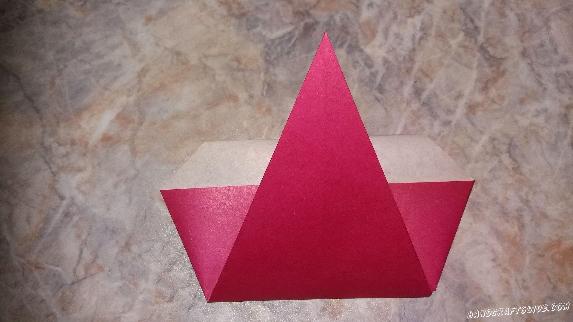 Переворачиваем нашу поделку, и боковые отступы от треугольника мы заворачиваем вперед