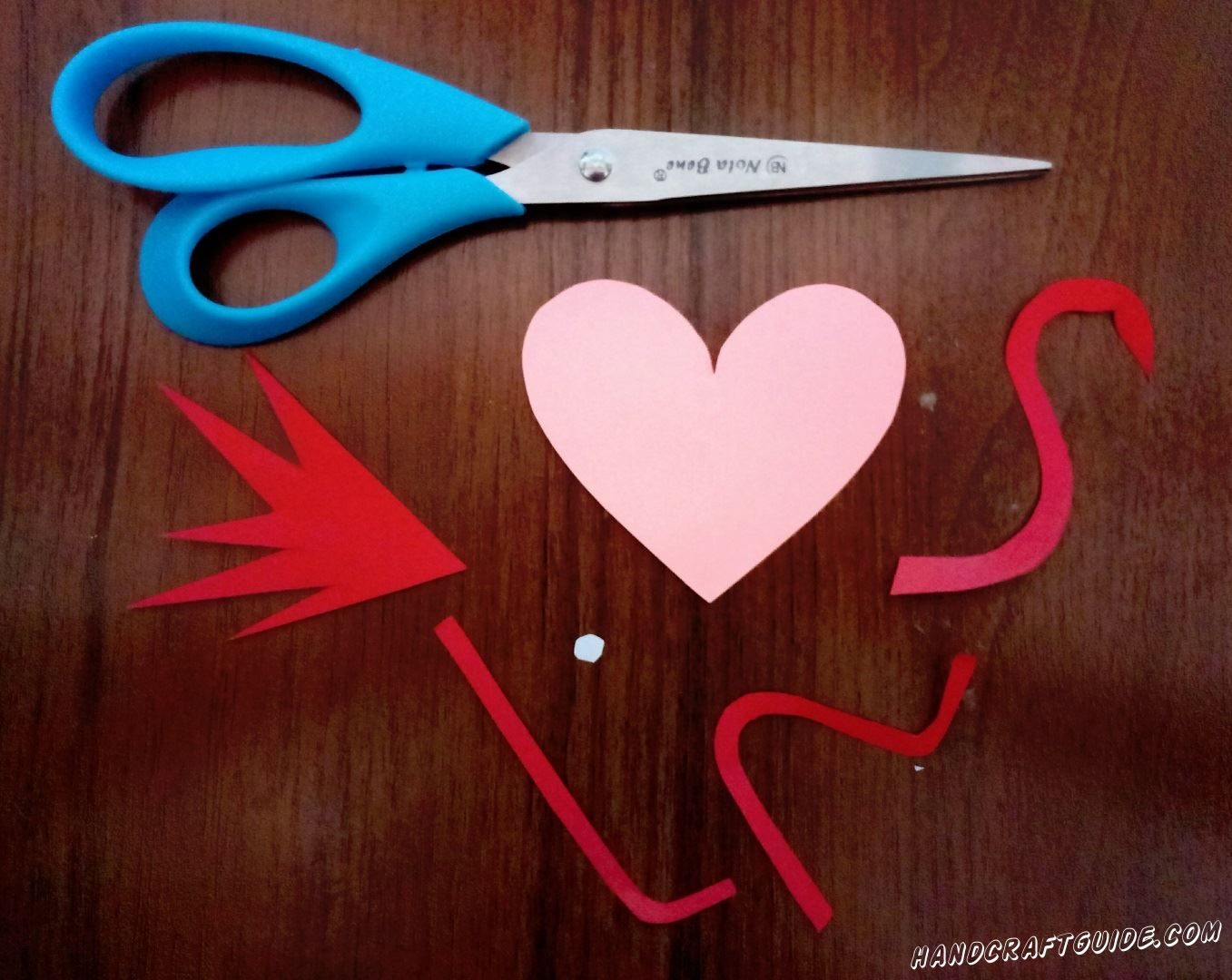 First we cut out the heart from pink paper. Then from red paper 3 wavy lines (legs and neck) and one tail + small eye.