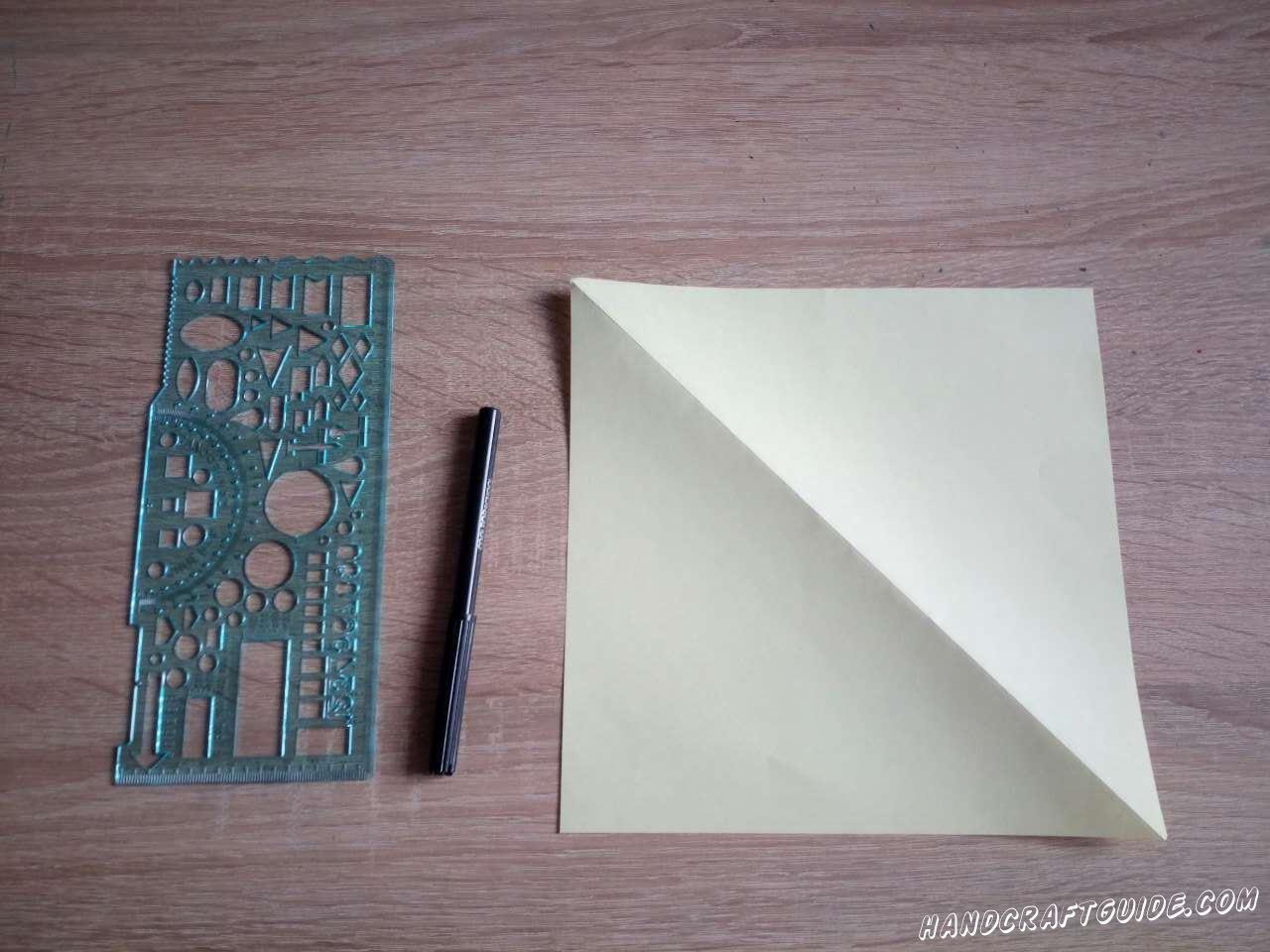 Берём светлую бумагу для оригами или вырезаем квадрат из обычной. Сгибаем в треугольник и разворачиваем