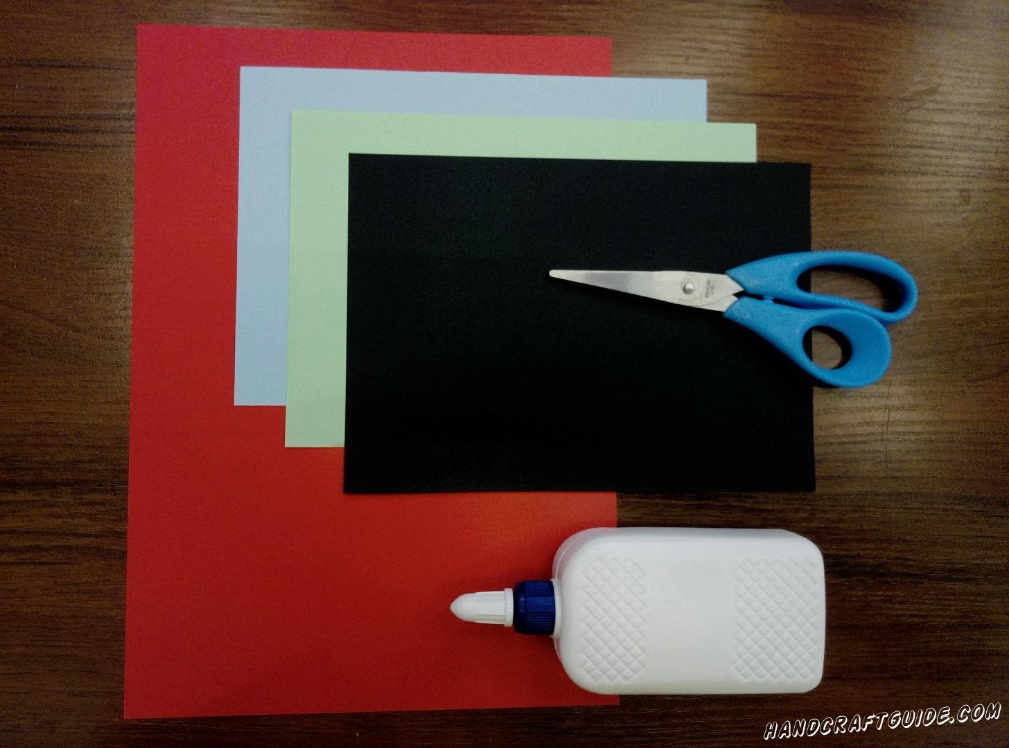 Для изготовление нам понадобится: Клей ПВА Ножницы Цветная бумага: красный лист формата А4; половинки листа А4 голубого, чёрного и бирюзового цвета