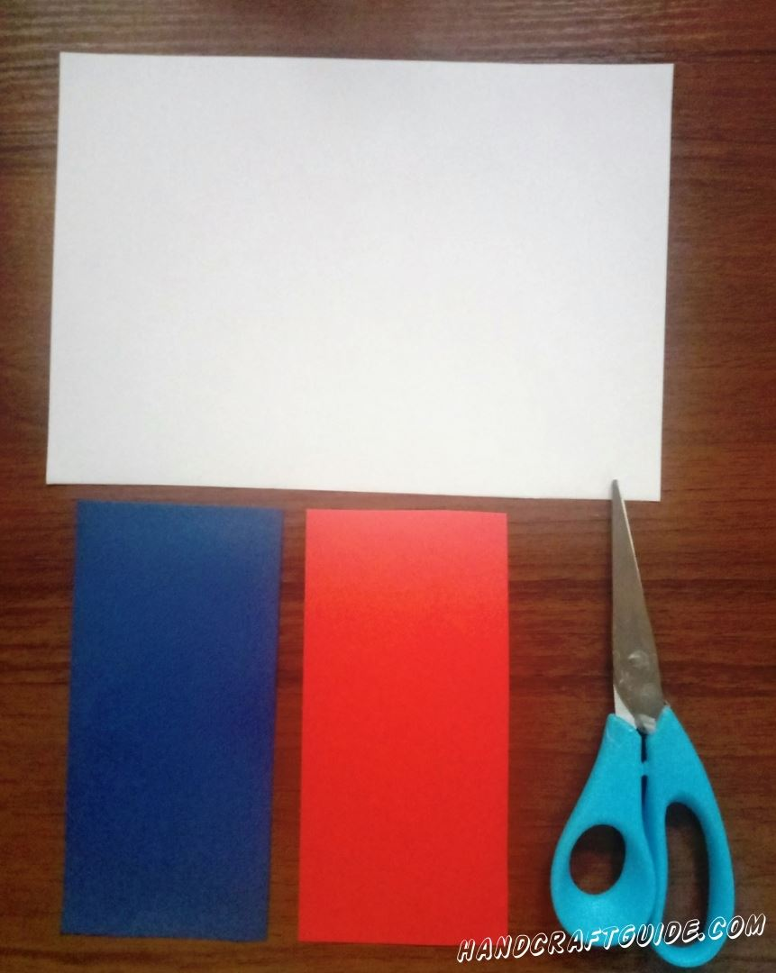 Take a blue sheet of paper and cut off 1/3 of it horizontally. To find out how much this is, you can use a ruler :) Then cut out the same piece from the red paper. It is easier, because you just need tu put the blue piece over the red paper and cut it.