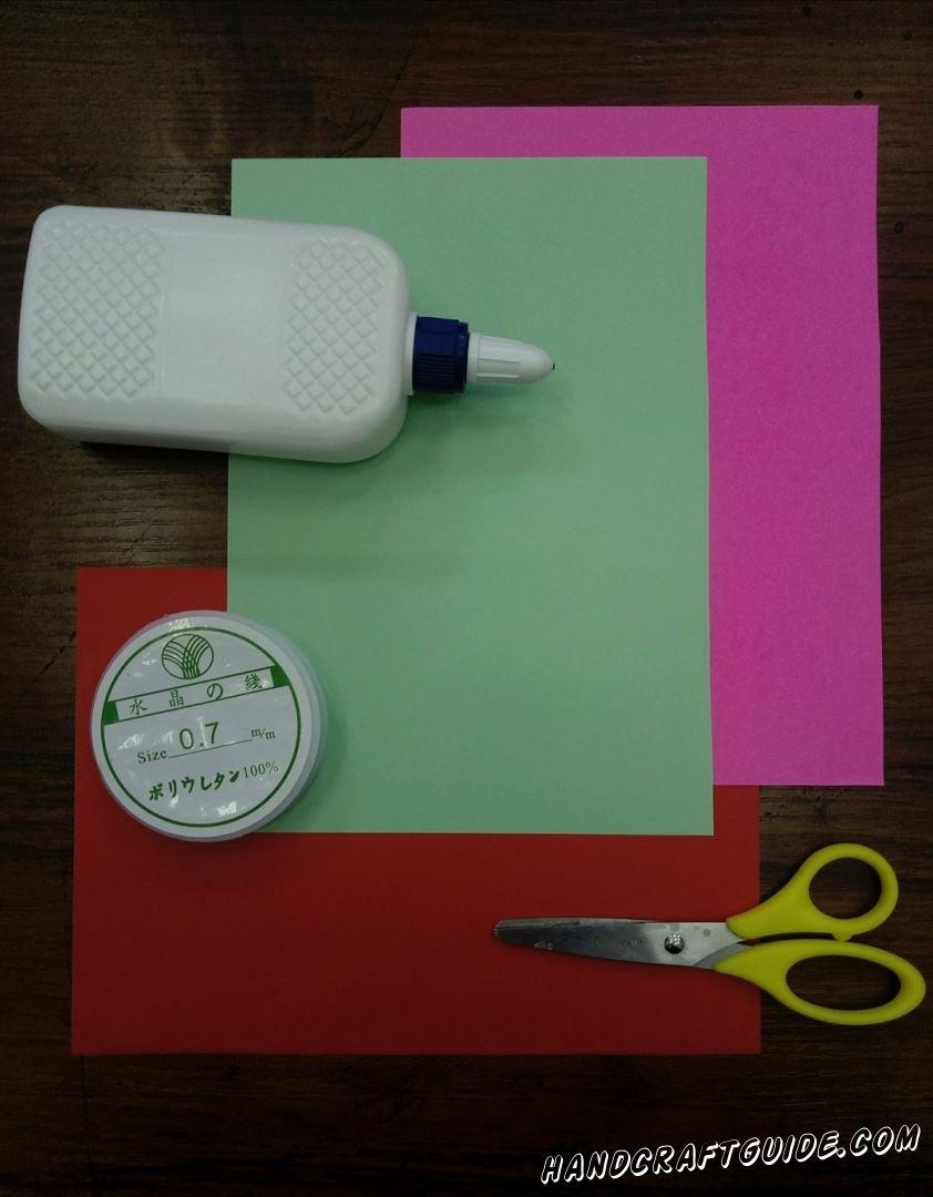 Для этого нам понадобится: Листы плотной цветной бумаги: бирюзовый, сиреневый, красный Ножницы Клей ПВА Леска (нитка, верёвка, резинка)
