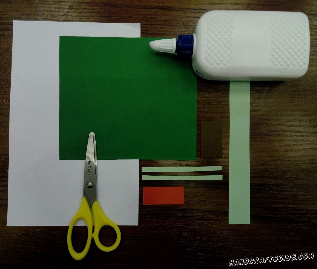 As usual we start with the preparation of all necessary details. Cut a square, which will be our background later, out of green paper. Take turquoise paper and cut out a wide (around 2.5 cm width) and 2 small thin stripes. Finish with cutting out one small red rectangle and brown one.