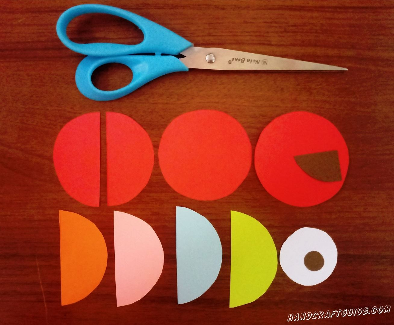 First we need to cut 3 identical red circles, one of which, then cut in half. Also we cut out 4 semicircles of the same size and different colors. Then we need a smaller white circle and a very small brown or black. Well, at last we need to cut out the beak.