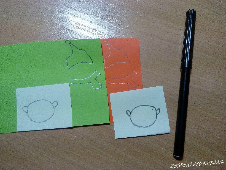 Рисуем на белой бумаге 2 кружка с ушками. Затем под размер белых кружков рисуем 2 шапочки 2 шарфика, салатового и красного цвета (по 1 каждого цвета). Вырезаем нарисованное