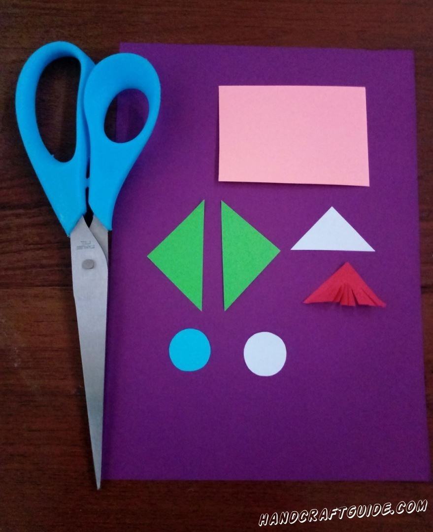First we cut out 2 identical green triangles, slightly smaller white and red. Blue and white circle. Finally, we cut out the pink rectangle and on one side of the red triangle we make many small incisions