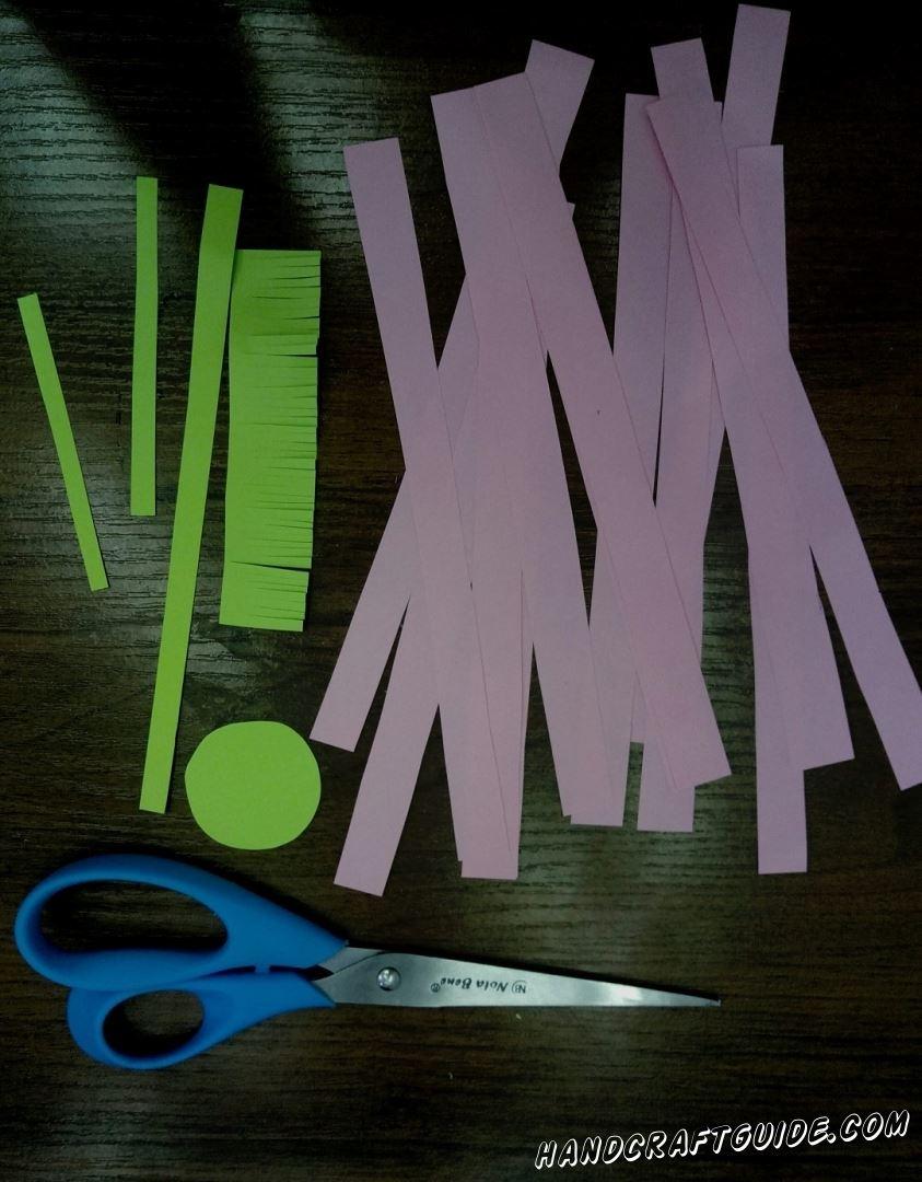 Для начала возьмем розовую бумагу и нарежем множество полосок, шириной в 1 сантиметр. Переходим к салатовой бумаге и нарезаем 2 маленькие тонкие полоски и 1 длинную, немного шире маленьких. Затем вырезаем кружочек и широкую полоску. На широкой полоске делаем множество надрезов с одной стороны. На этом подготовка окончена, переходим к самому интересному