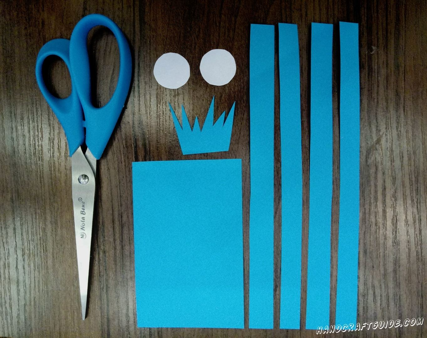Cut out little figures of the blue construction paper like it is shown in the picture.