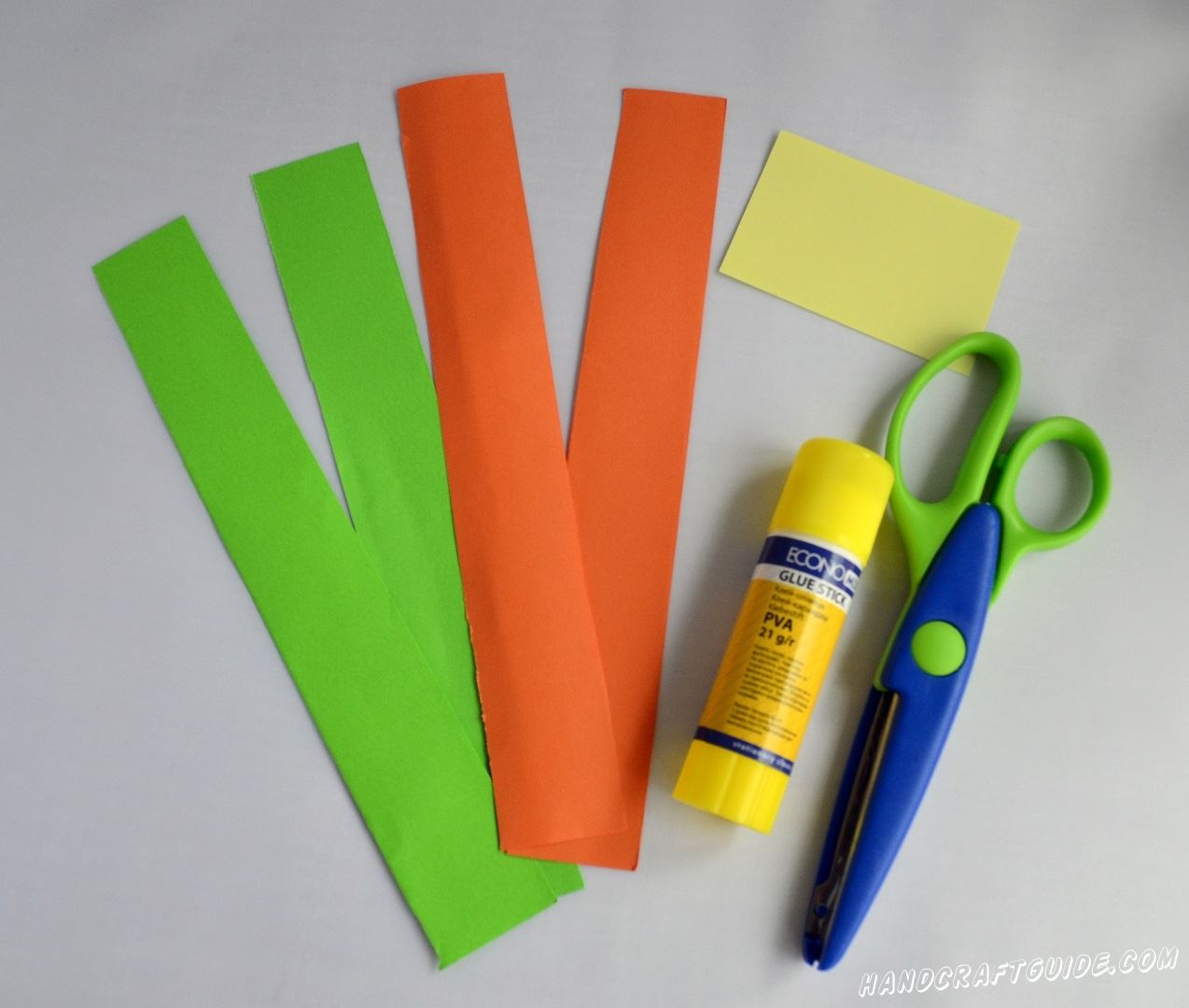 Вырезаем две полоски любимого цвета (мы взяли оранжевую и зелёную) и склеиваем их с одной стороны, расположив оранжевую вертикально, а зелёную - горизонтально.