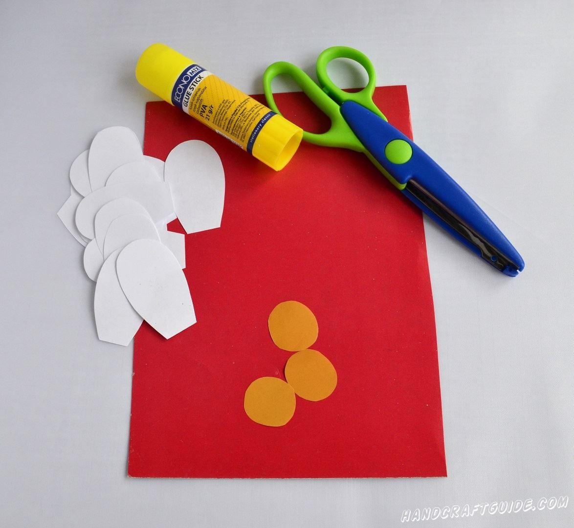 Расположим перед собою лист красной бумаги в горизонтальном положении. Теперь берем белую бумагу и вырезаем 18 лепестков как у ромашек. Ещё нам нужно 3 маленьких кружочка оранжевого цвета.