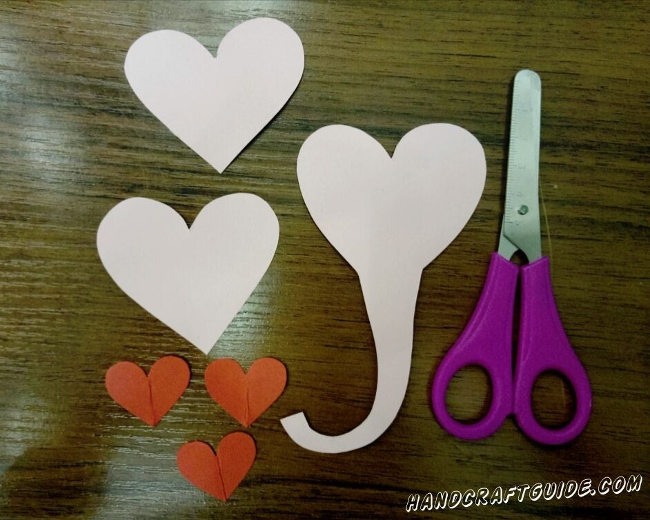 First, we cut out 3 small hearts from red paper, 2 large ones from pink and one of the same size, only with a proboscis on the sharp end.