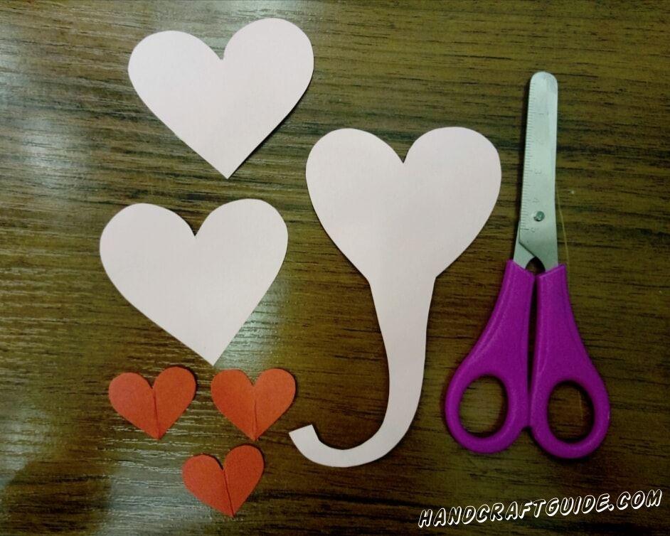Для начала мы вырезаем 3 маленьких сердечка из красной бумаги, 2 больших из розовой и одно такого же размера ,только с хоботком на остром конце.