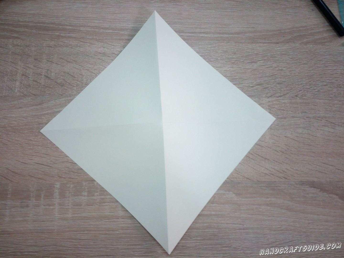 Cut a square sheet out of colored paper. Fold it into 4 parts and unfold it as shown in the photo.