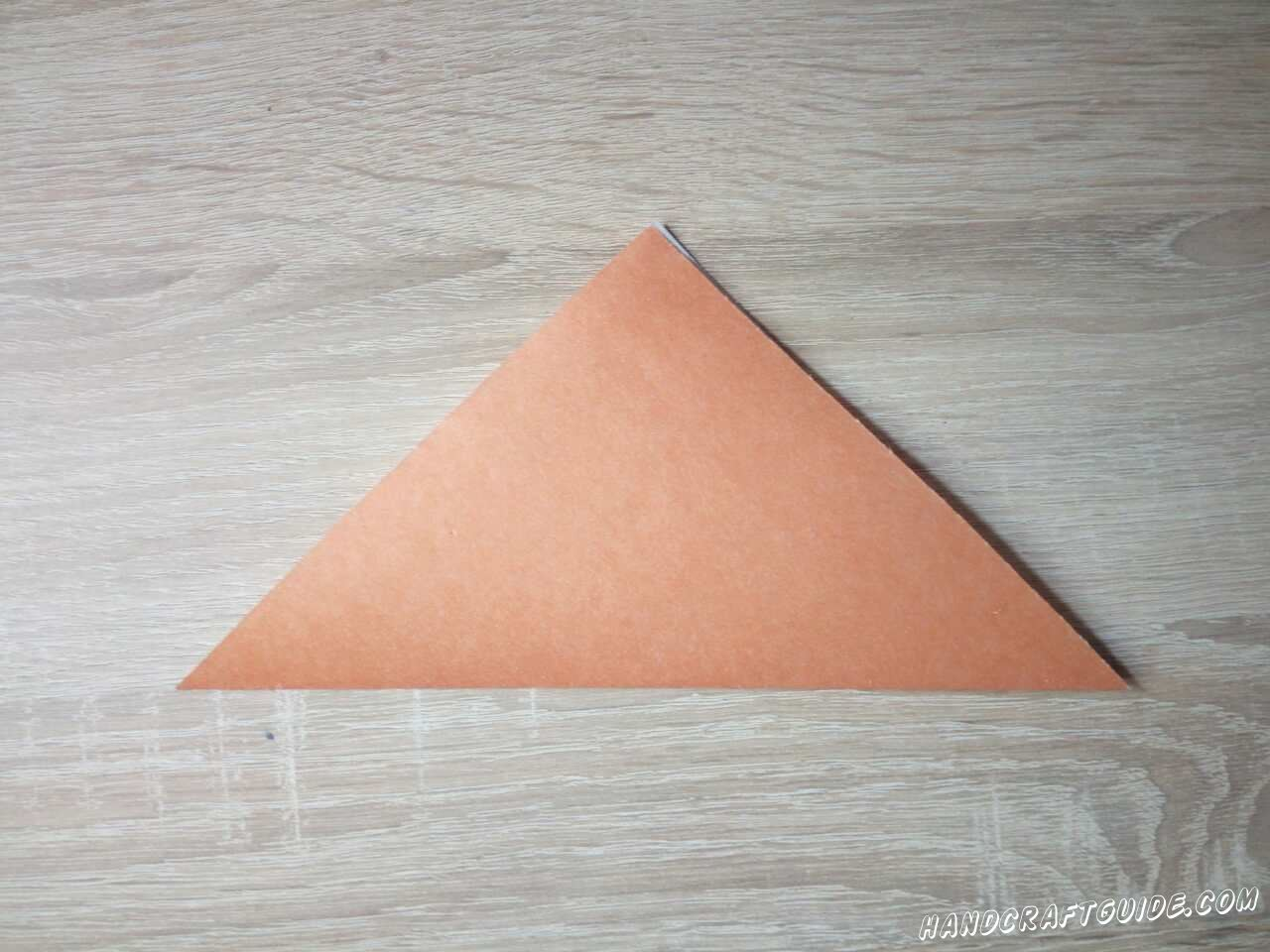 Из цветной бумаги вырезаем квадрат. Складываем его пополам в треугольник