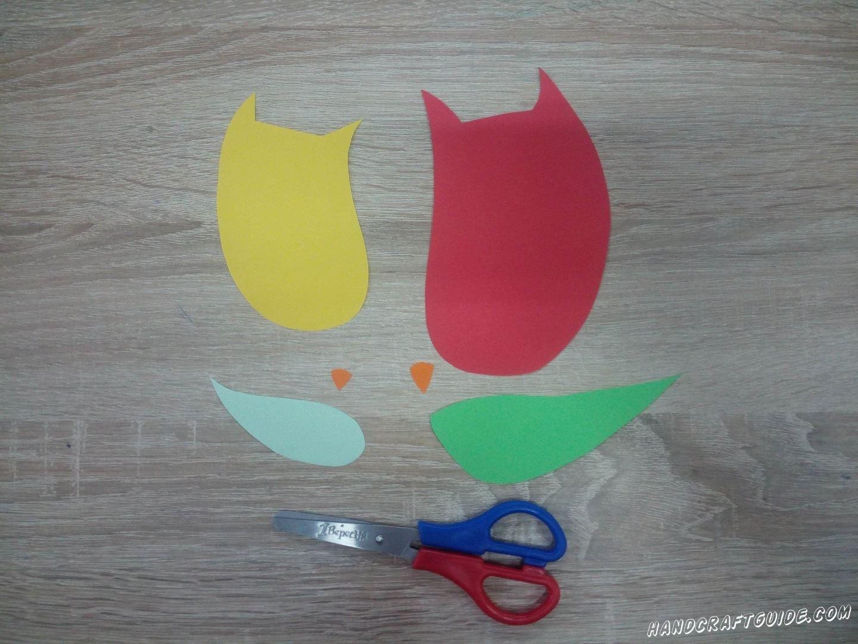 Для начала вырежем все необходимые детали. Из красной бумаги вырезаем большой овал, с острыми ушками на одной стороне. Затем, такой же формы, но меньших размеров из желтой бумаги. Затем вырезаем 2 крылышка, большое - зелёного цвета и голубое маленькое крылышко. Напоследок подготовки вырезаем 2 маленьких оранжевых клювика