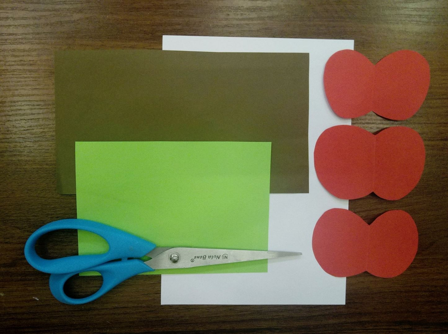 Для начала вырезаем три яблочка одинакового размера, из красной бумаги