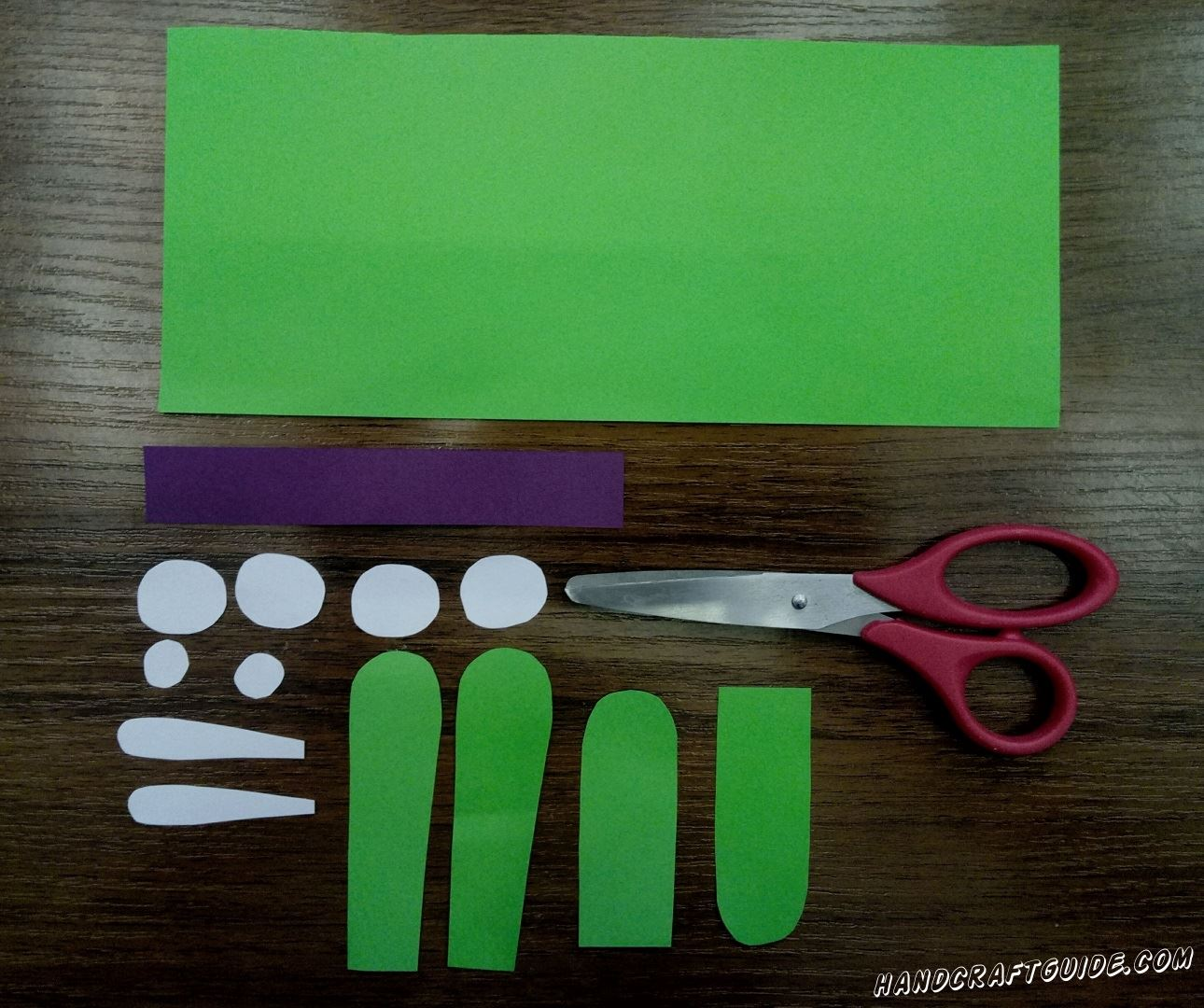 Для начала нам нужно подготовить все необходимые детали. Берем зелёную бумагу и вырезаем 1 прямоугольник, 2 ушка и 2 лапки. Затем берем белую бумагу и вырезаем 4 небольших кружочка, 2 кружка совсем маленького размера и 2 вставочки для ушек. Ещё нам понадобится небольшая полосочка фиолетового цвета