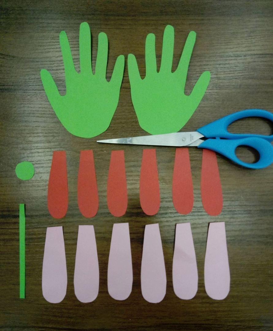 Для начала нам нужно подготовить все необходимые детальки. Берем зелёный лист бумаги и обводим свою ладошку 2 раза. Вырезаем то что нарисовали. Также из зелёной бумаги нам нужна тонкая полосочка и кружок. Затем вырезаем 6 деталек, похожие на ушки зайца, розового цвета и таких же 6 деталей красного цвета
