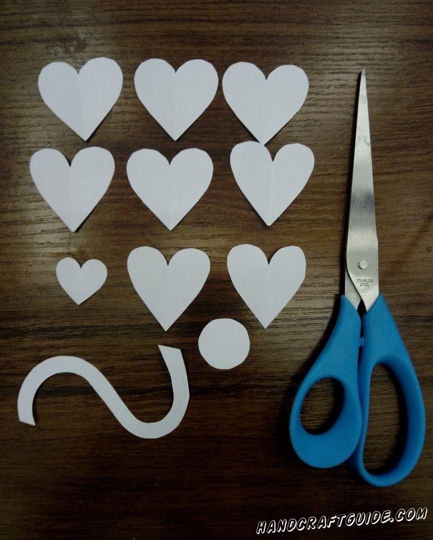 Для начала подготовим все необходимые нам детальки. Берем белую бумагу и вырезаем 8 сердечек одинакового размера, 1 сердечко меньшего размера,1 небольшой кружок и 1 волнистую полоску. Вырезаем также маленький оранжевый клювик
