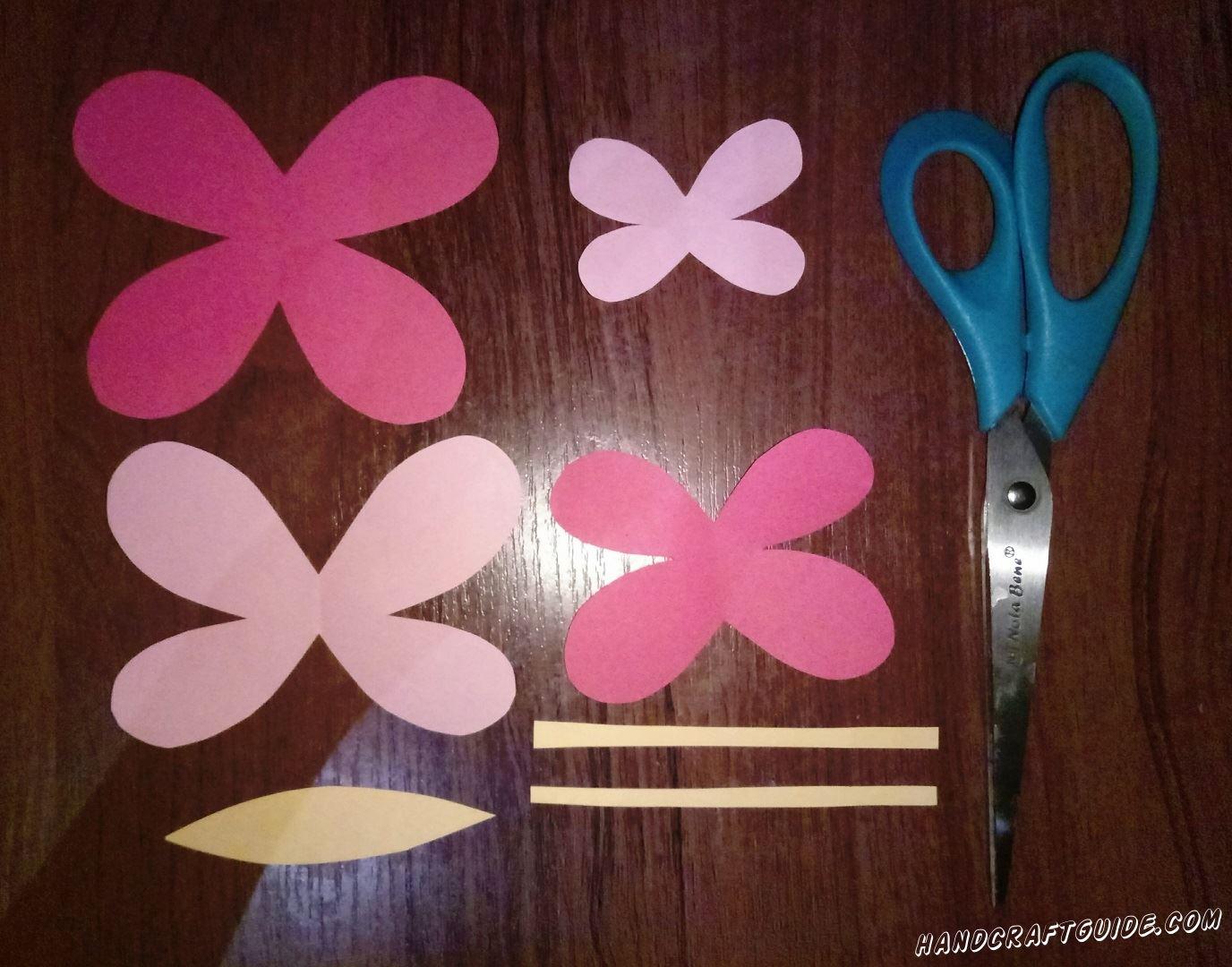 Для начала нужно вырезать все необходимые детальки. Берем розовую бумагу и вырезаем детальку в форме цветочка с 4 лепестками, одну большую и одну маленькую. Такие же детальки вырезаем из светло-розовой бумаги, только большая будет немножко меньше большой розового цвета, а меленькая - меньше розовой маленькой. Также вырезаем 2 тонкие полосочки и детальку в форме листика, желтого цвета.