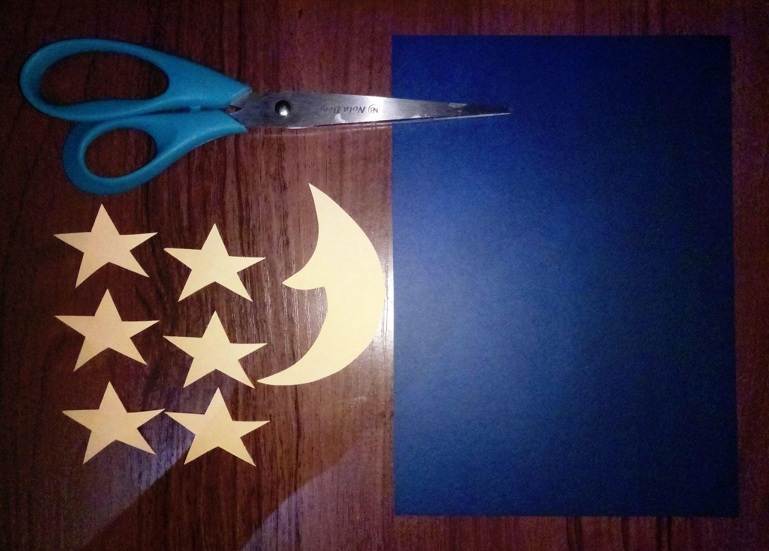 Для начала возьмем лист синей бумаги, он послужит нам фоном. Затем вырезаем звёздочки и полумесяц из желтой бумаги