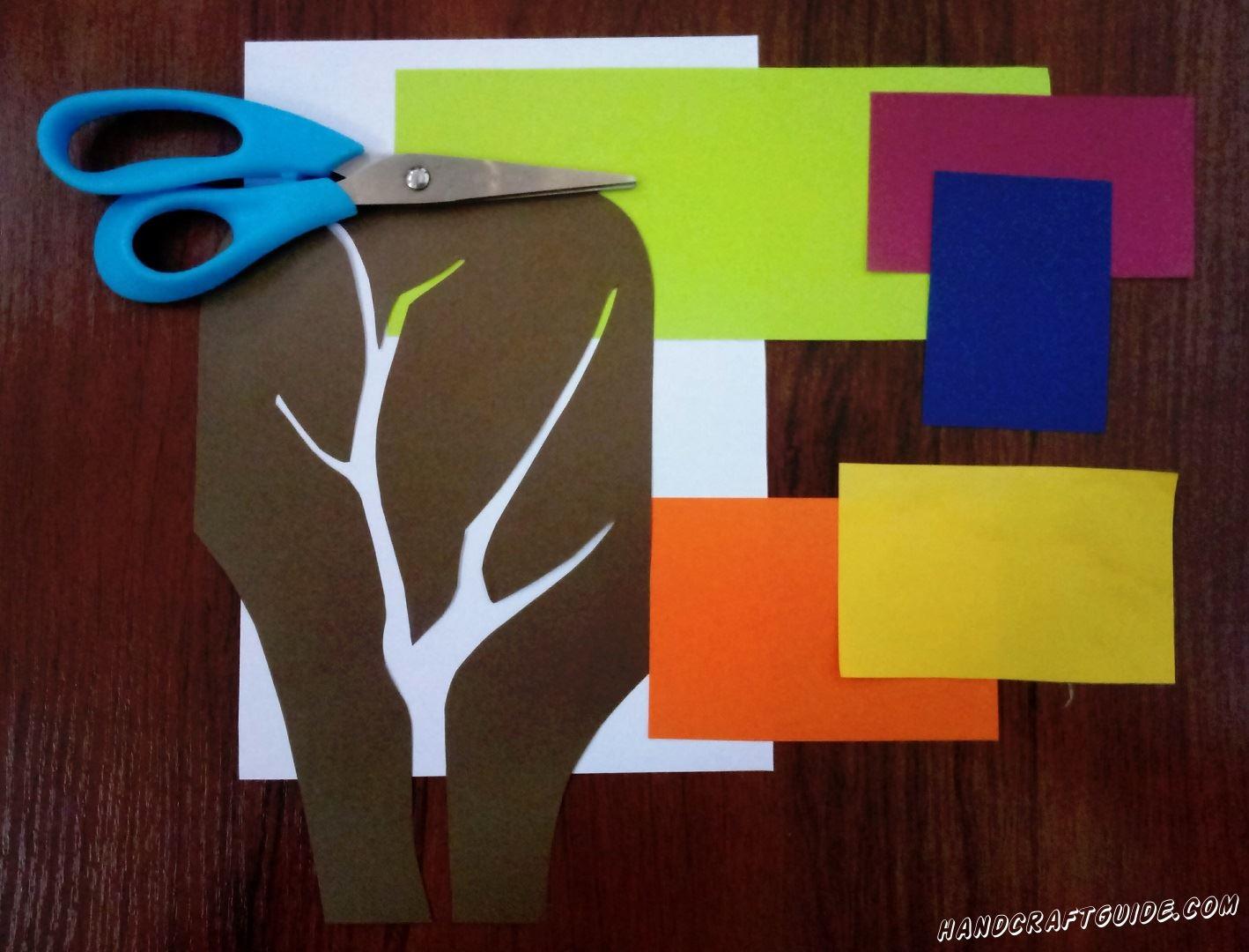 Для начала вырезаем все необходимые детали. На коричневой бумаге рисуем дерево только с ветками без листьев и вырезаем его, оставляем себе фон, а не само дерево. Затем берем салатовую бумагу и вырезаем 10 листочков. Затем вырезаем фигурки в форме крылышек птичек. Нам нужно 2 большие желтого оранжевого цвета и 2 маленькие - синего и розового цвета.