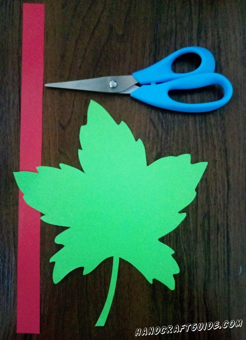 Вырезаем кленовый листочек из зелёной бумаги и длинную красную полоску