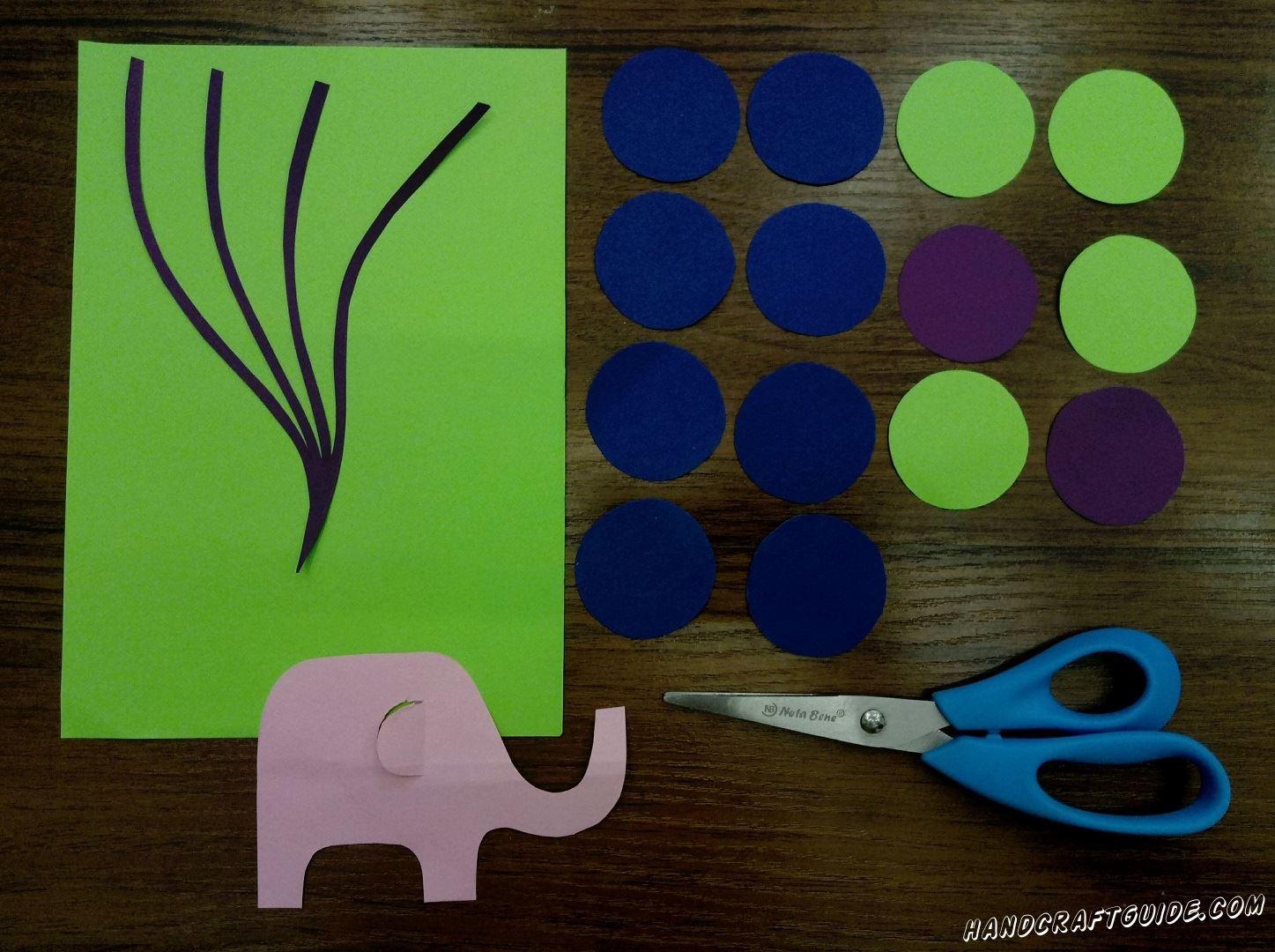Для начала нужно вырезать все необходимые нам детальки. Берем синюю бумагу и вырезаем 8 одинаковых кружков. Такого же размера вырезаем 4 салатовых 2 фиолетовых кружка. Далее, из фиолетовой бумаги, вырезаем 4 волнистые тоненькие полосочки с одним общим концом. Ну и последняя фигурка розового цвета в форме небольшого слоника. Переходим к шагу №2