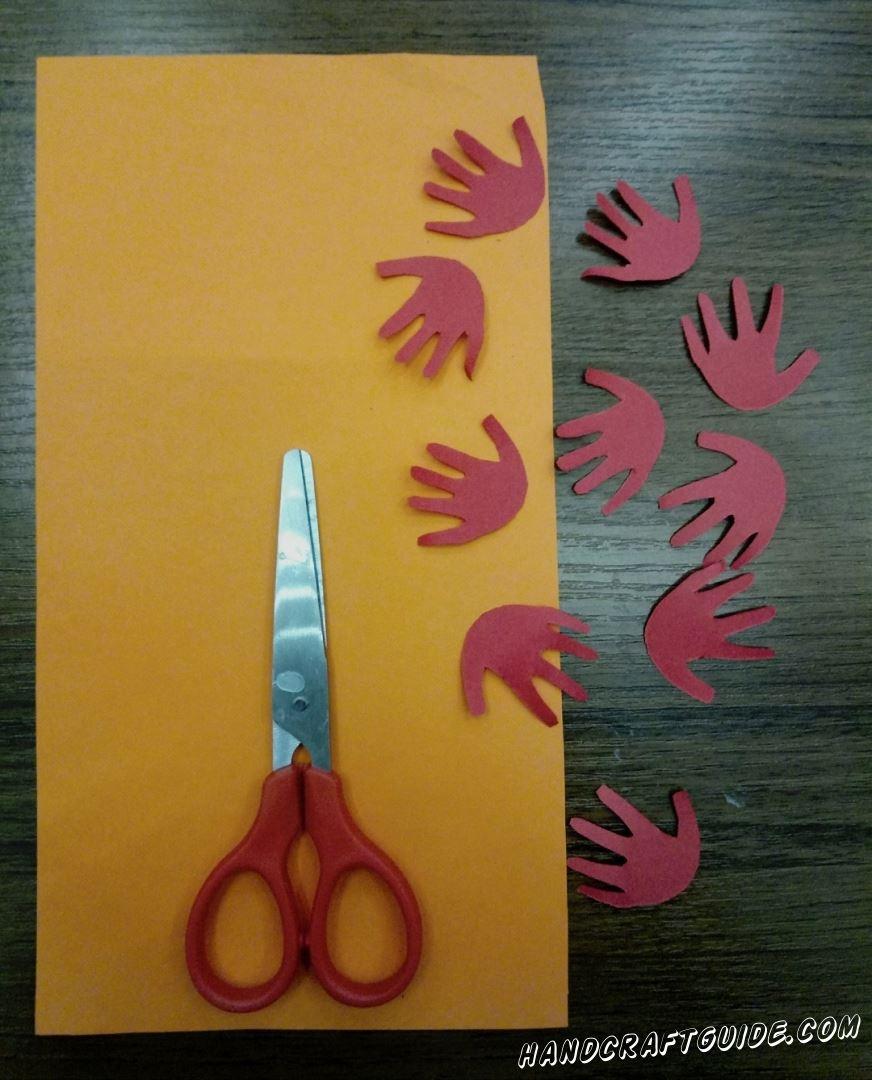 Из красной бумаги вырезаем множество маленьких ладошек