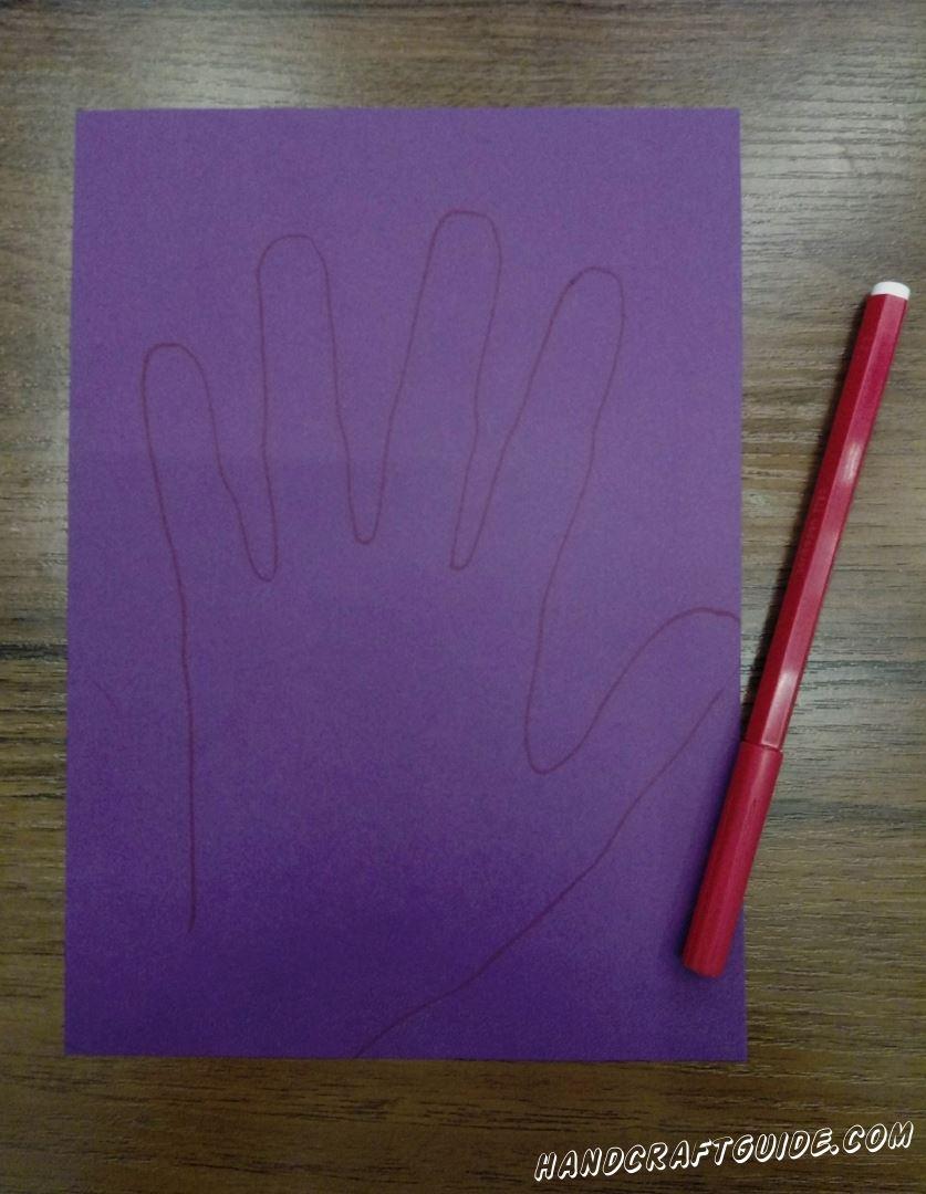 Для начала,  на фиолетовой бумаге нужно обвести свою ладошку
