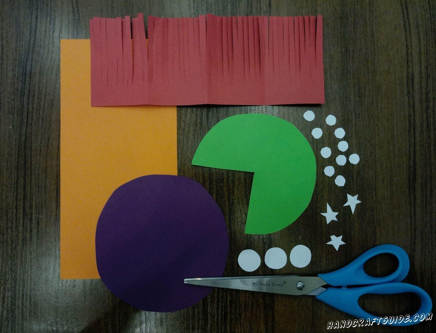 Для начала нам нужно подготовить все необходимые детали. Вырезаем фиолетовый круг, оранжевый прямоугольник, красный прямоугольник, на котором делаем множество надрезов, с одно длинной стороны, зелёный круг с вырезанным углом.Затем вырезаем 3 маленьких звёздочки, 3 кружочка и 10 совсем маленьких кружков белого цвета