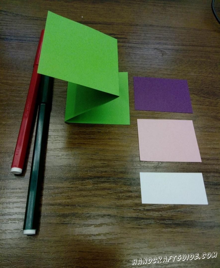 Из цветной бумаги вырезаем все необходимые нам детали, как на фото. Складываем зелёную полоску в 3 раза, так чтобы верхняя часть была чуть длиннее остальных