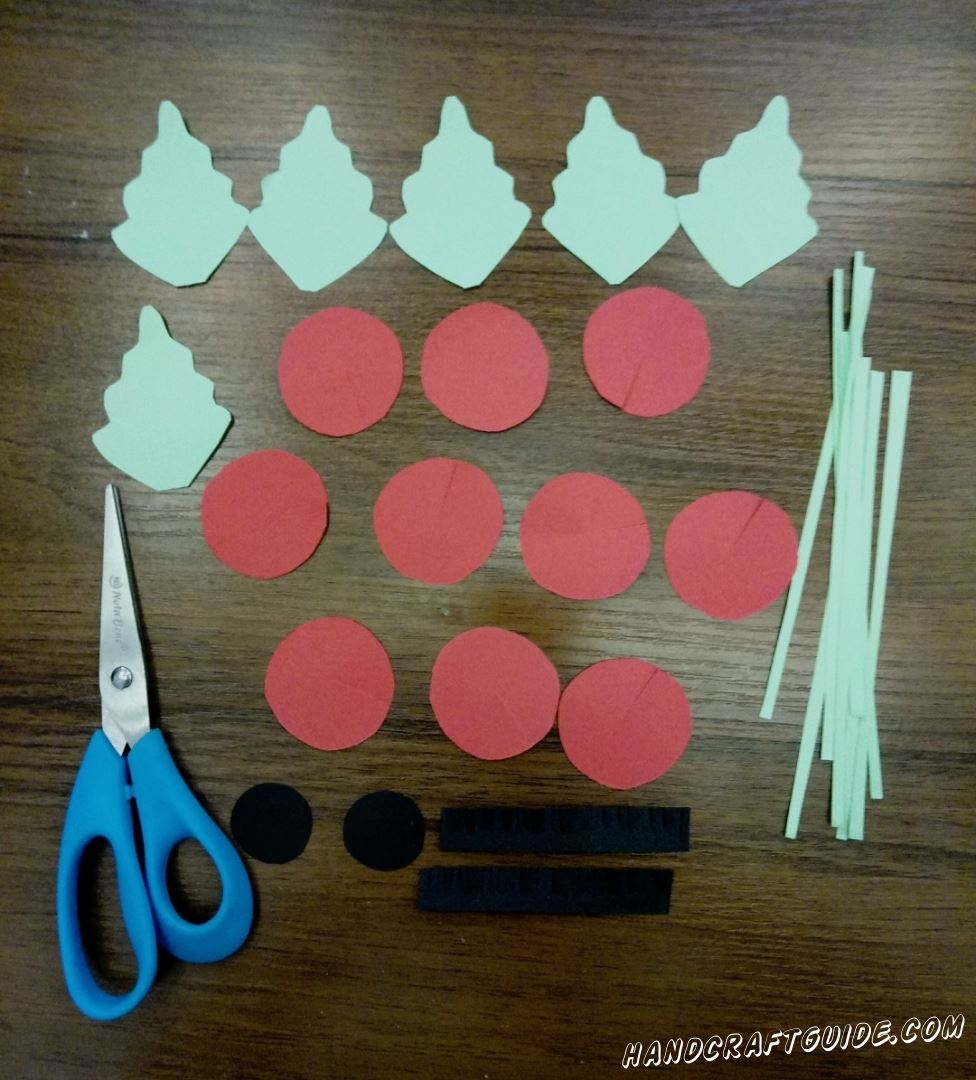 Let's take turquoise paper and cut out 6 leaves, with wavy edges and a lot of thin strips. Then take red paper and cut out 10 identical circles which need to be cut to the centre. It's time to take black paper and cut out of it 2 small circles, 1 very samll small circle and 3 stripes which need to have a lot of small incisions. Well done! The most difficult is done. Let's continue...
