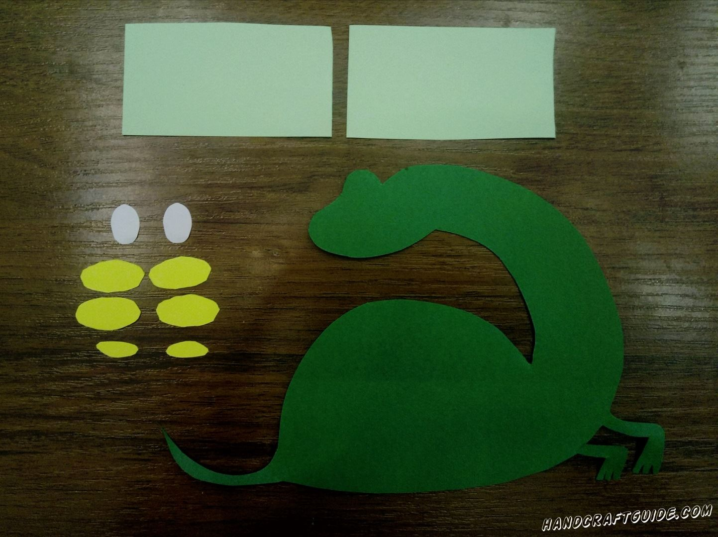 To begin with take green paper. Draw a dino on it and then cut out what you've drawed. You can see an example on the photo. The next step is to cut out yellow ovals, you can make them different sizes. Then take the turquoise paper and cut out 2 small rectangles. In the end cut out 2 white ovals for the eyes.