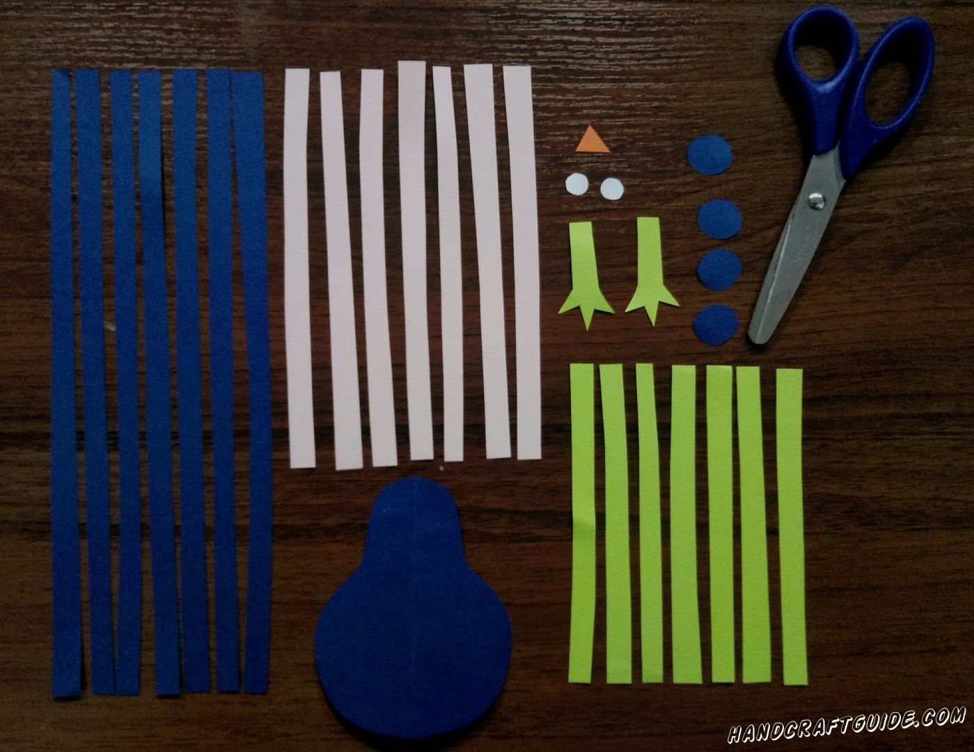 First, we need to cut a blue detail similar to number 8, but without the holes inside. Cut out seven long blue stripes and to finish with this color, cut out 4 small circles.  Next take pink paper and cut out 7 stripes a little shorter than the blue ones. To finish our preparations make 7 short green stripes, 2 paws, 2 white little circles and a very small orange triangle.