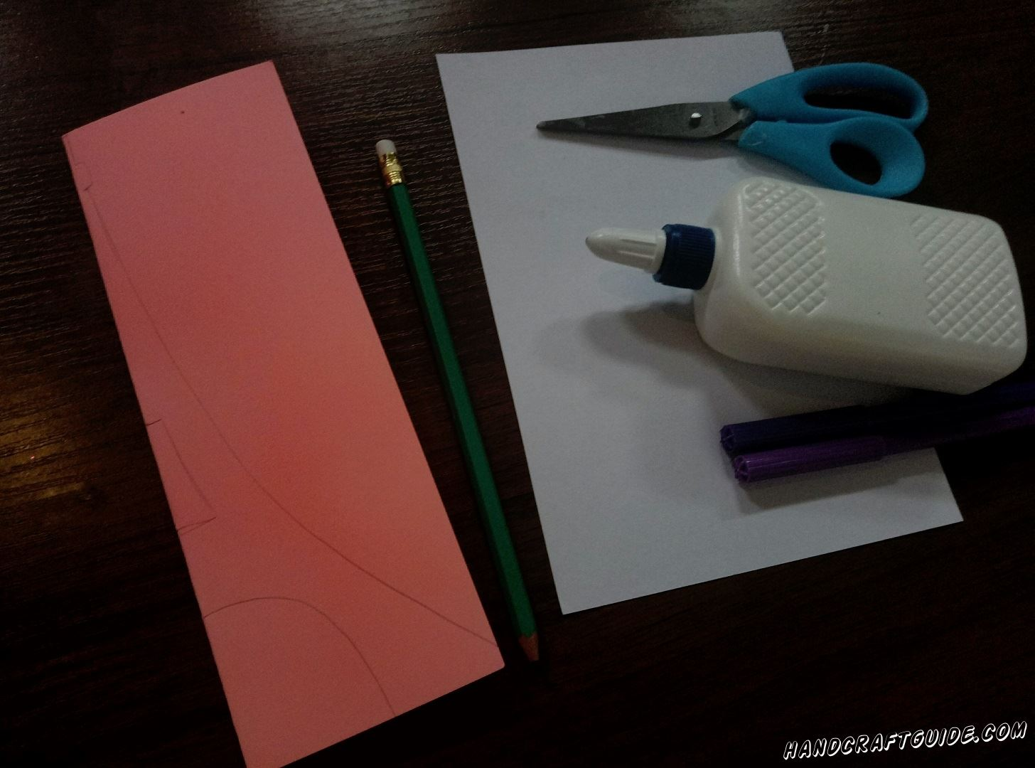 At the very beginning take a pink sheet of paper and vertically fold it in half . Then draw a half of the tower so that when you cut it out, you'll get a symmetrical figure.