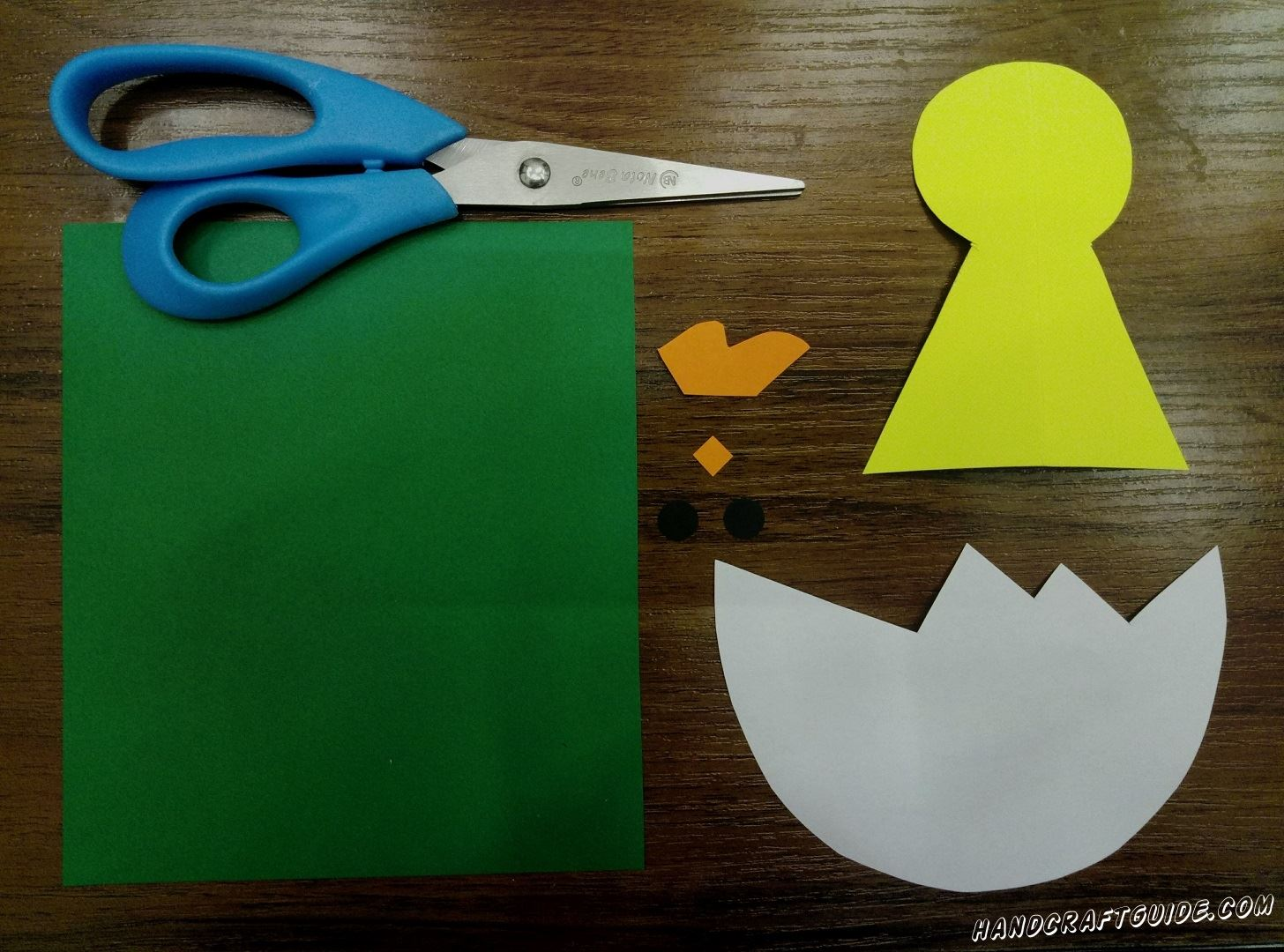 First, let's cut out the needed details. Take yellow sheet of paper and cut out a figure similar to a keyhole, on top it's a circle with triangle beneath. Use white paper to make an eggshell. To do this, cut out a semicircle and make sharp edges on the flat side. Cut a comb and a small square out of orange paper. The last one cut out 2 small circles and take a green paper for the background.