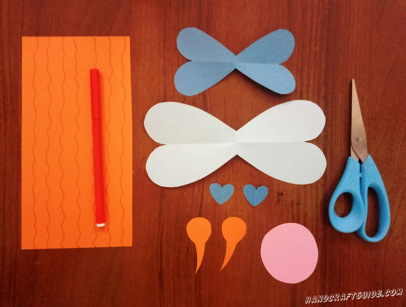Cut the wings out of white paper and the smaller ones out of blue paper, cut out 2 blue hearts, pink circle and 2 orange circles with tails.Draw wavy lines on the orange rectangle.