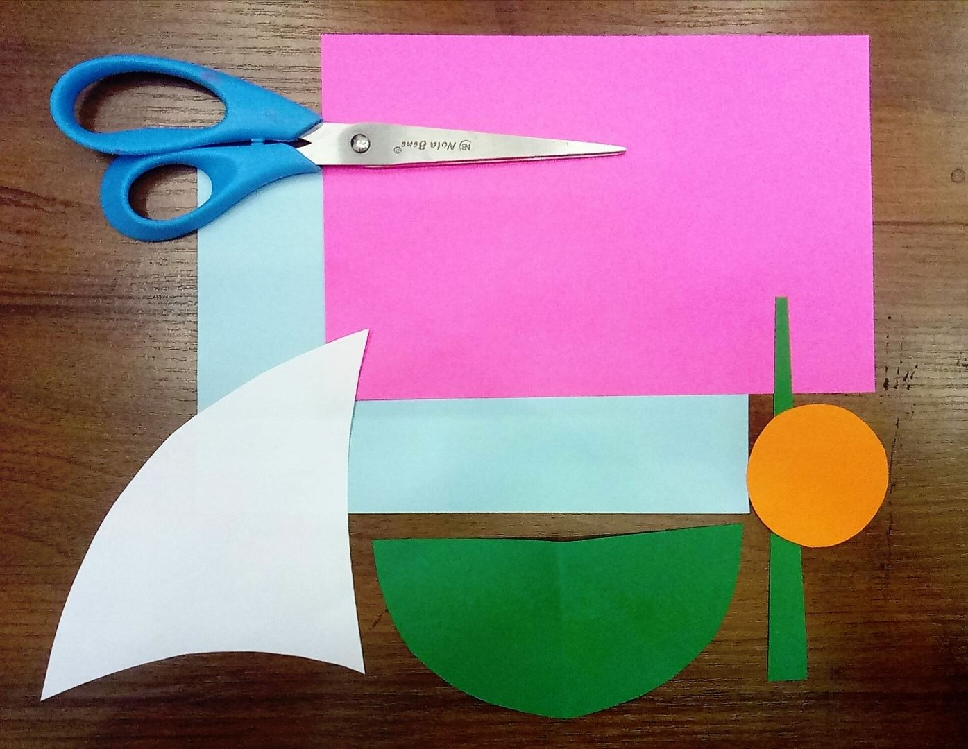 Начинаем с того,что подготовим все необходимые нам детали. Из белой бумаги мы вырезаем парус, напоминающий плавник акулы:) Затем нам нужно вырезать оранжевый кружок и зелёный большой полукруг , к которому добавляем небольшую сужающийся полоску. Готово, идём дальше