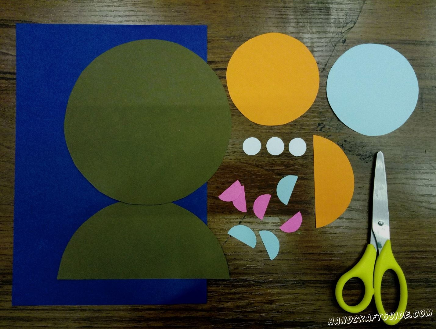 First, cut out all the needed details. Start from cuting out a large brown circle and and a semicircle of the same size. Then do the same with the orange paper, just this time cut out circle 3 times less. Cut out a blue circle, identicale to orange one, and 3 small semicircles. Out of pink paper cut 4 small semicircles of the same size as blue ones. Finish your preparation with three small white circles and take a blue sheet of paper, which serves as a background. It was not easy, but you did a great job! L