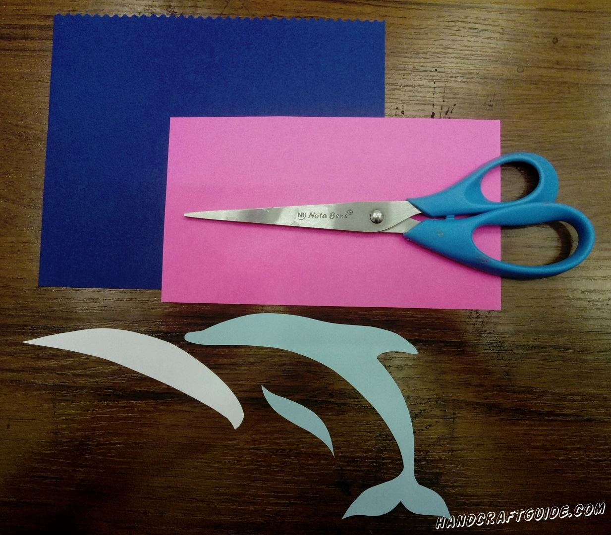 First, take a blue paper and scissors. Cut out a thin body of your dolphin and a small wavy fin. Also cut out a blue belly for your dolphin that perfectly fits the body. Well done. Now using figured scissors cut off a strip from a blue sheet of paper. If you don't have figured scissors use regular scissors and make waves.