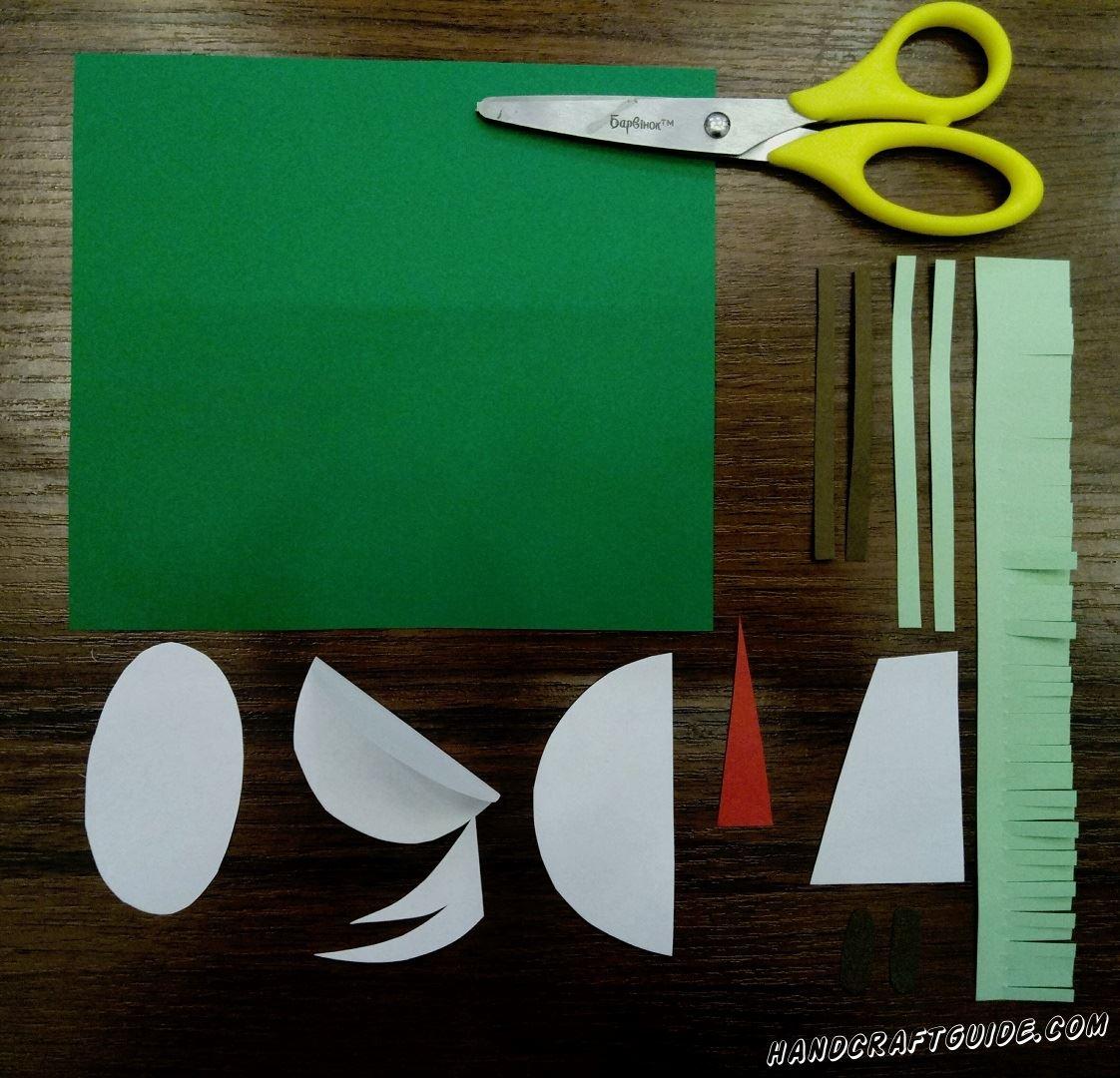 Начинаем мы, как всегда, с подготовки всех нужных на деталей. Из зелёной бумаги вырезаем большой квадрат, который далее будет служить нам фоном. Из бирюзовой бумаги вырезаем одну широкую (примерно 2,5 см в ширину) и 2 маленькие тонкие полосочки. Закончим подготовку тем, что вырежем маленькие красный и коричневый прямоугольники.