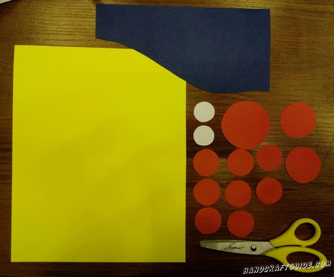 Для начала мы берём синий лист бумаги и вырезаем из него прямоугольник, только чтоб одна сторона была волнистой, а не ровной, как будто горка. Из красной бумаги мы вырезаем 1 круг покрупнее, 2 чуть меньше и 8 чуть меньше средних. Затем, из белой бумаги, 2 самых маленьких кружка. Ну и не забываем взять желтый лист, он нам послужит фоном