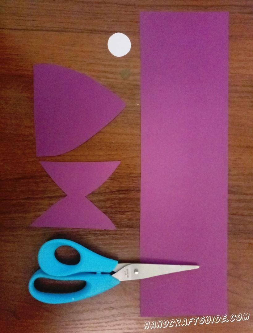 Для начала мы вырезаем маленькие кружочки из коричневой и белой бумаги. Затем , из фиолетовой бумаги, вырезаем широкую полоску. После чего , так же из фиолетовой бумаги, вырезаем немного закруглённый треугольник и фигурку , напоминающую песочные часы. Готово, можем продолжать...