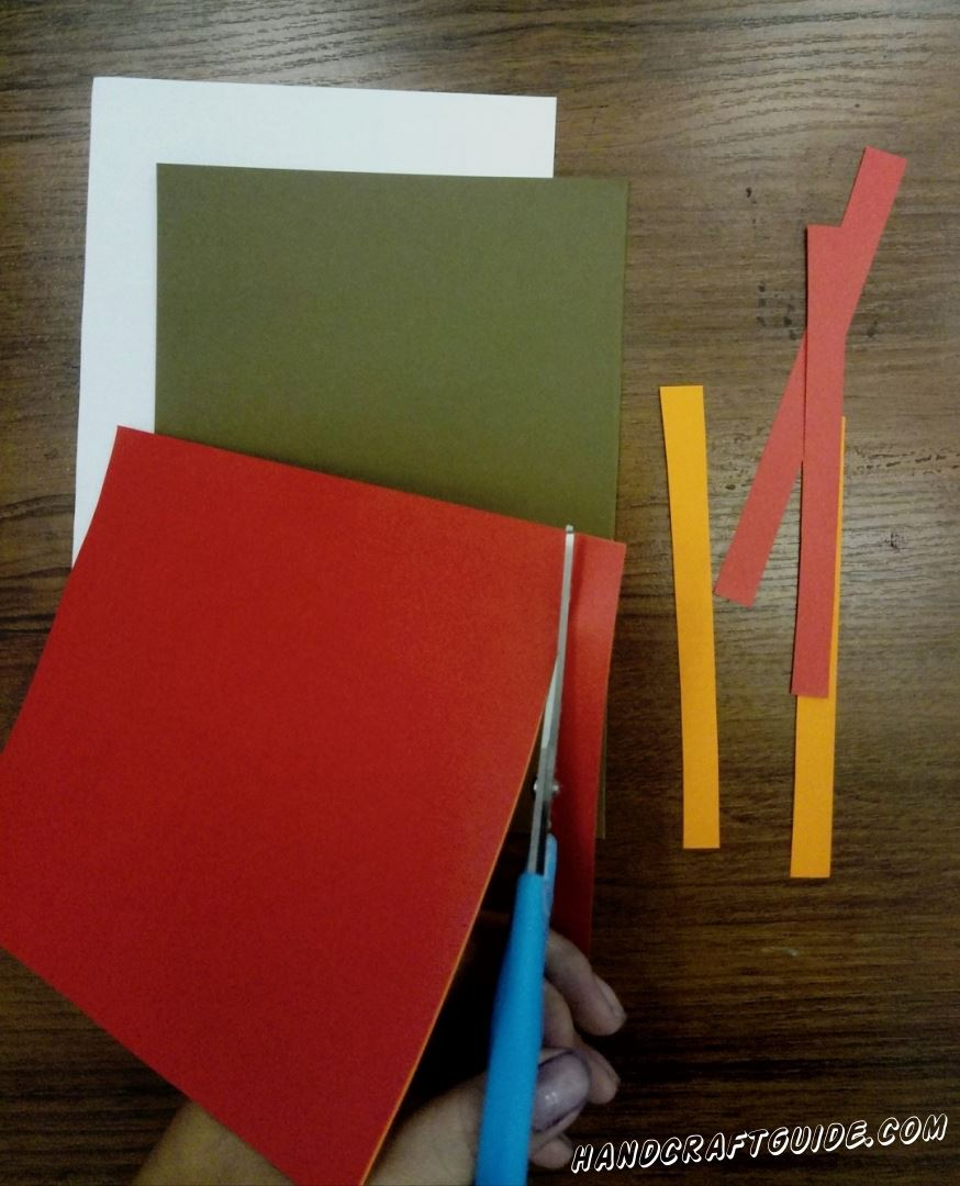 First, put together orange and red paper. Cut out many stripes. Using brown paper cut out a tree's trank with branches.