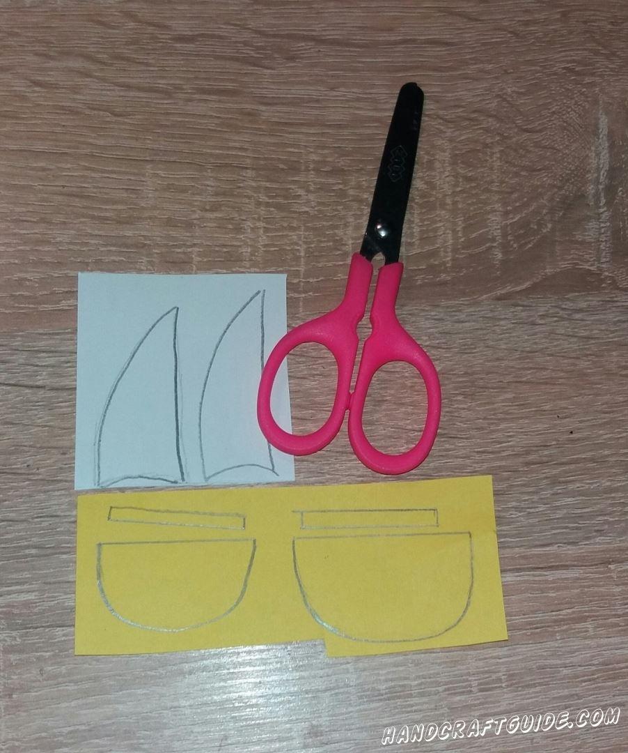 Для начала подготовим все нужные нам детали. Берем белую бумагу и вырезаем 2 паруса. Затем берем бумагу желтого цвета и вырезаем 2 полукруга и 2 полосочки.