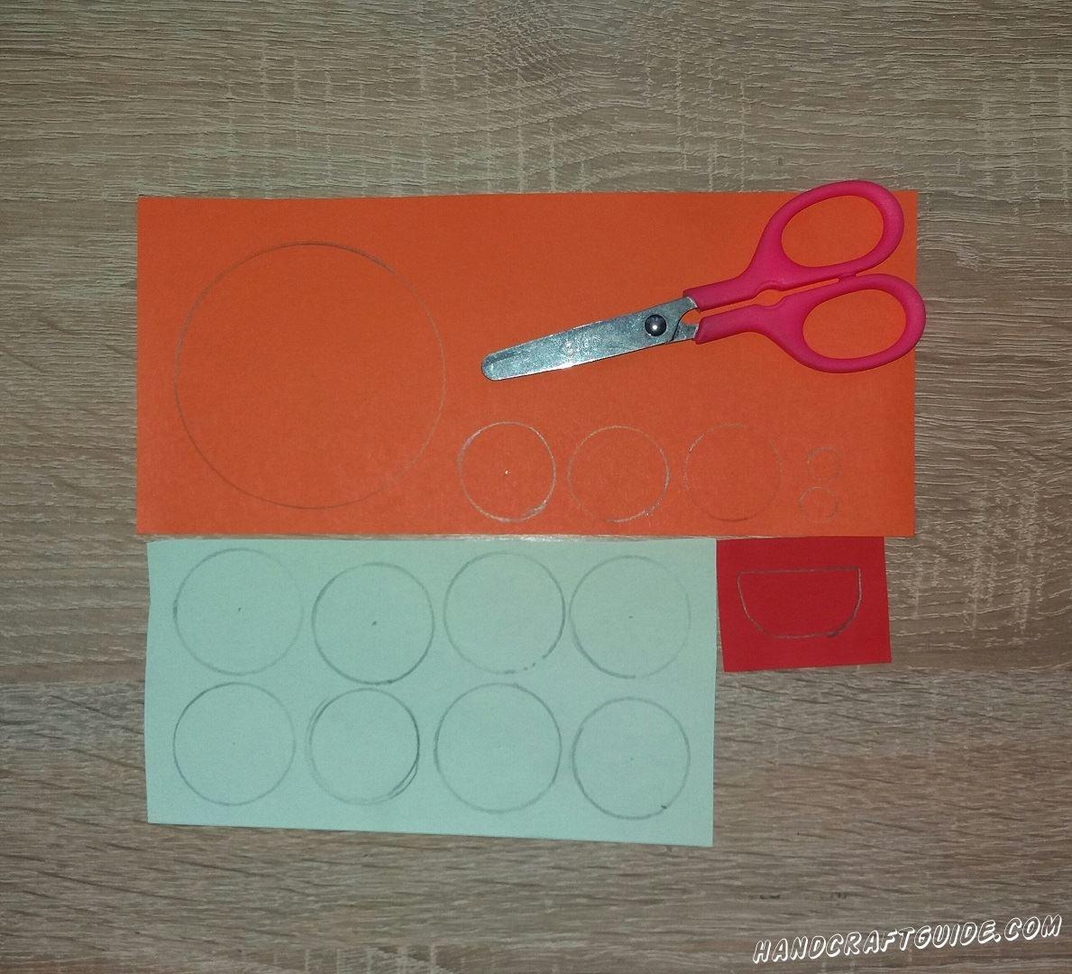 Подготовим все необходимые детальки для выполнения поделки. Для начала возьмем в руки светло-зеленую бумагу и вырежем с нее 8 одинаковых кружков. Затем из оранжевой бумаги вырезаем 3 кружка такого же размера, как и зелёную, 1 большой круг, 2 совсем маленьких круга,2 небольшие полоски и 2 клешни. Из красной бумаги вырезаем один полукруг. Когда подготовка завершена, можем переходить к самому веселому.