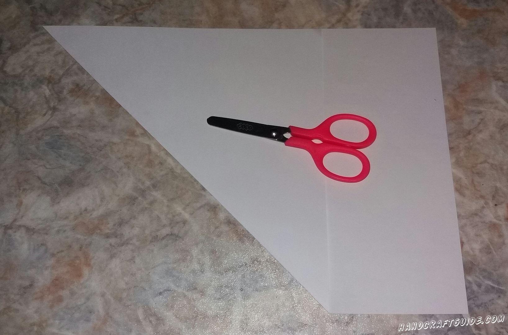 Вырезаем ровный квадрат из белого листа формата А4. Для этого загибаем ровный треугольник и вырезаем лишнее